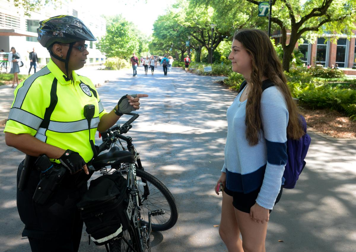 Tulane University Police Department officer talking to student